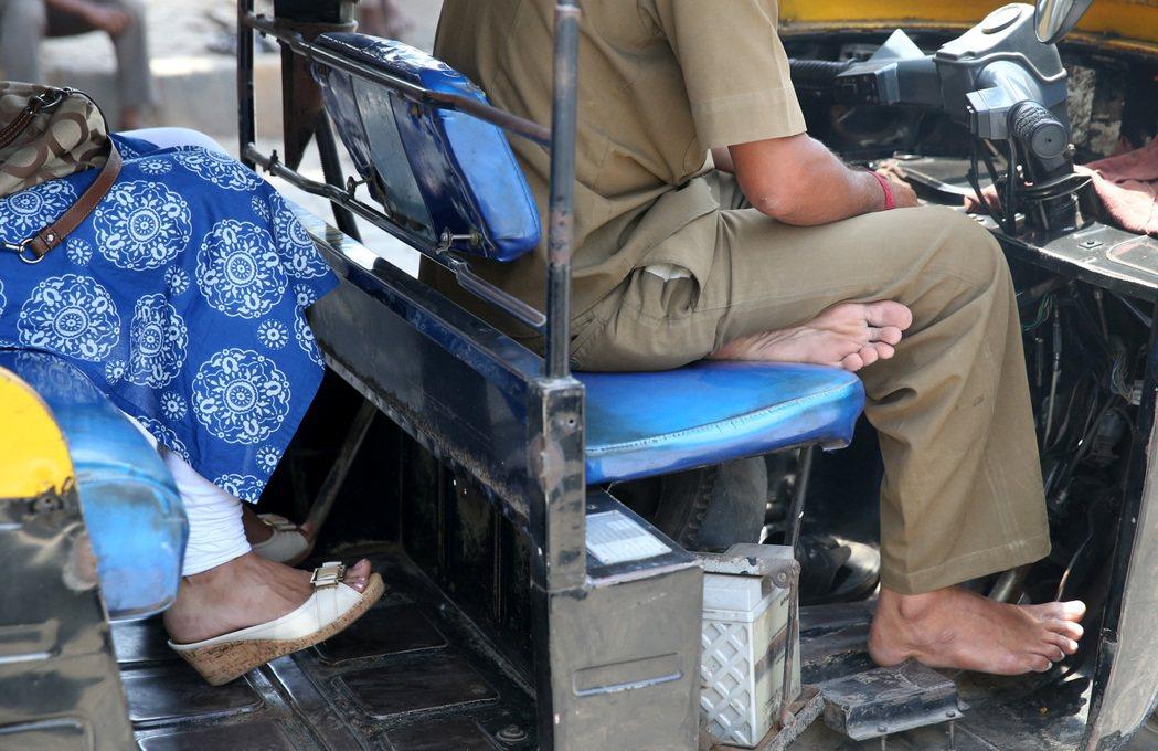 印度社會貧富差距大,階級分明,圖為打赤腳的嘟嘟車司機載著打扮亮麗的婦女。 記者潘...