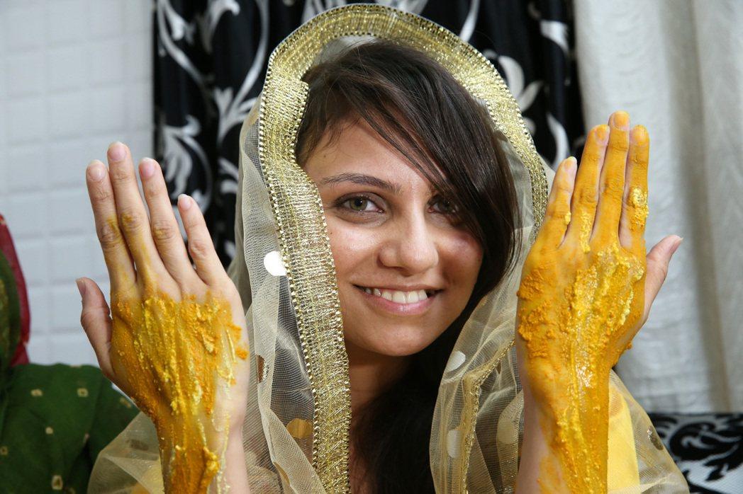 Rafia手上被親友塗滿薑黃等保養品。 記者潘俊宏/攝影