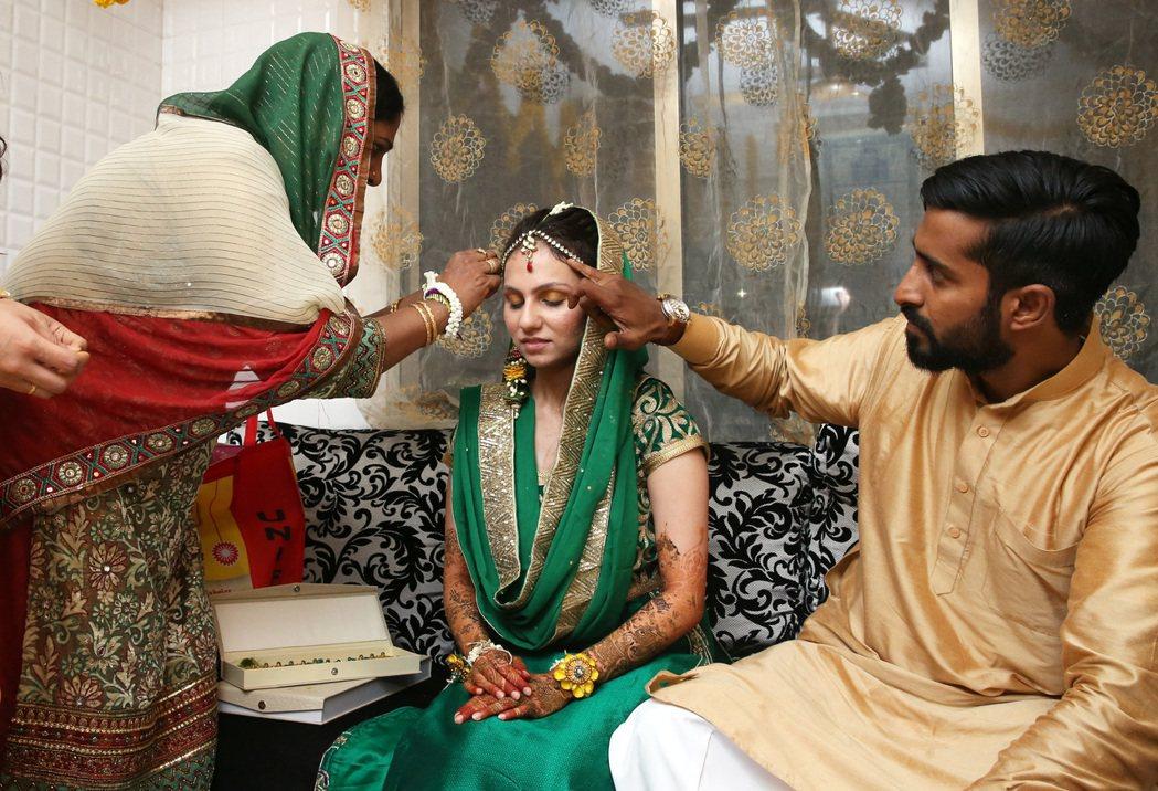 長輩為新娘子Rafia細心打理珠寶首飾,新郎在旁幫手。 記者潘俊宏/攝影
