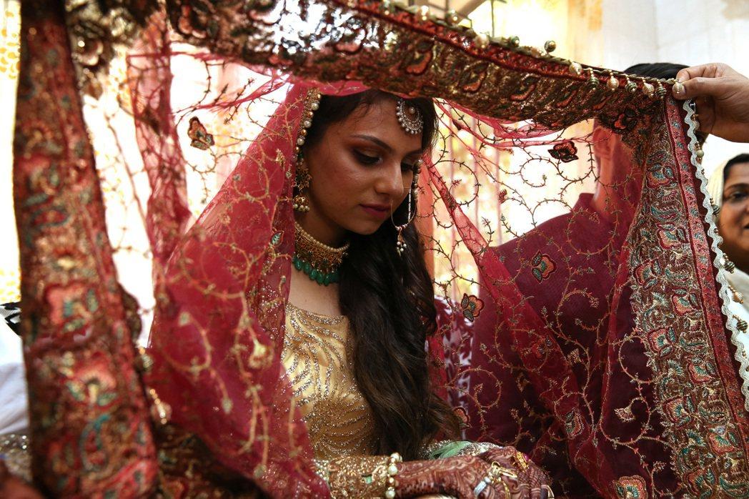 家族長輩替新娘子Rafia披上頭紗。 記者潘俊宏/攝影