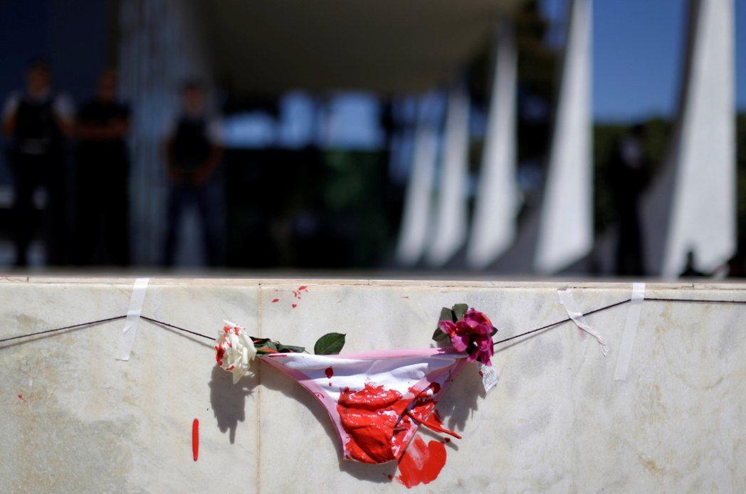 持花的示威者包圍了巴西最高法院,並突破了封鎖的拒馬,將鮮花擺放在正義女神忒彌斯雕...