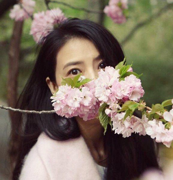 半張臉蛋兒藏在花朵後,圓圓標志的玲珑大眼被越髮凸顯。圖文:悅己網