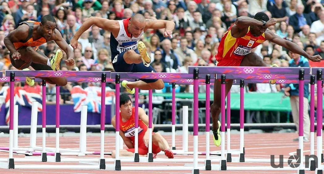 大陸選手劉翔(中下)在2012年倫敦奧運110跨欄預賽撞到第一欄而跌倒。記者侯永...