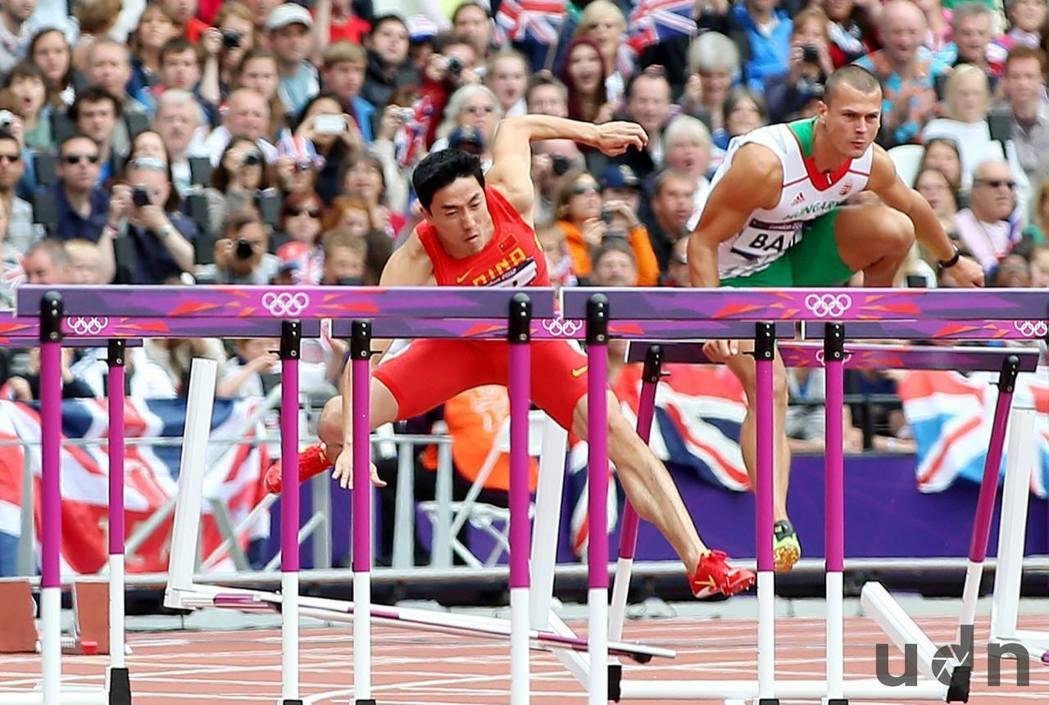 大陸選手劉翔(左)在2012年倫敦奧運110跨欄預賽撞到第一欄而跌倒。記者侯永全...