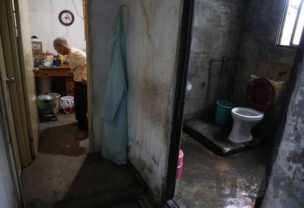 牆壁斑駁、燈光昏暗,塌陷的天花板下,是木板隔成僅容一床的小房間。記者林俊良/攝影
