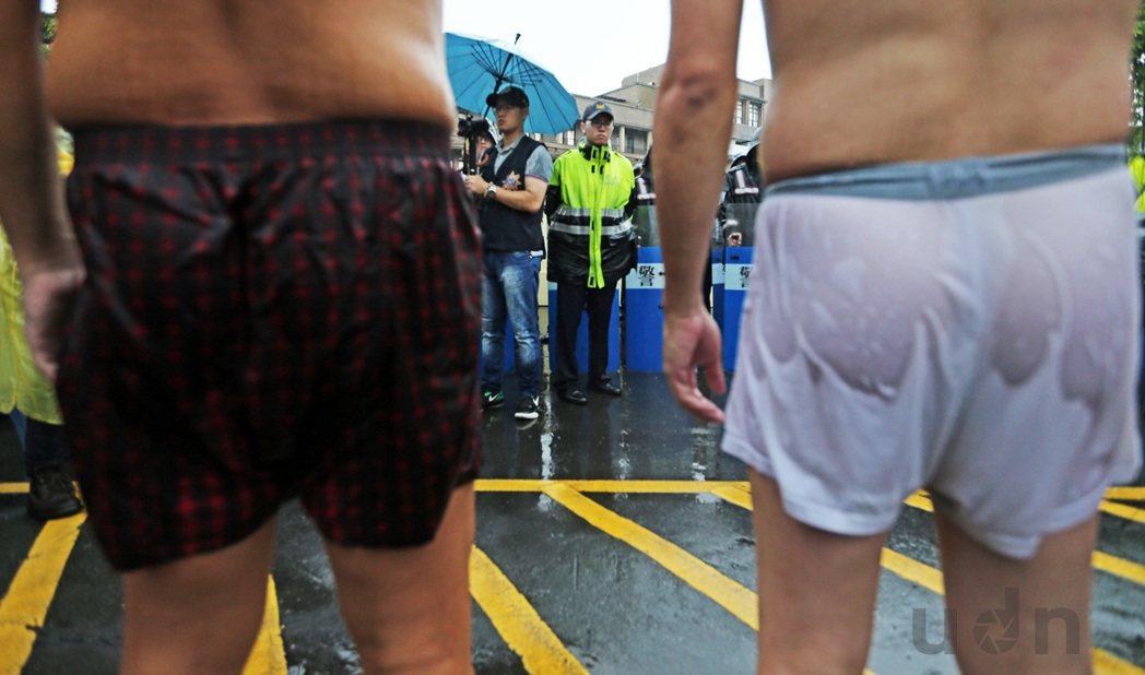 「不同的對焦點 敘述不同觀點」勞團成員在滂沱大雨中脫去所有衣服,在行政院前僅穿著...