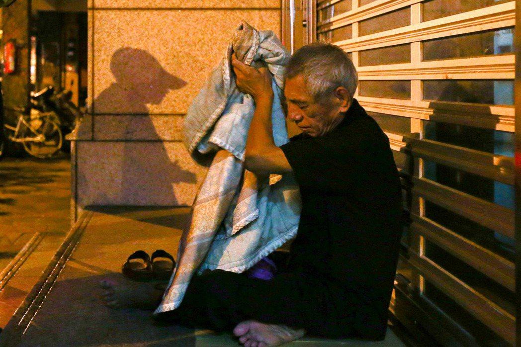 台北市萬華富福里台灣銀行前有兩位街友睡在走道上,被巡守隊員勸離,一人無奈地收拾行...