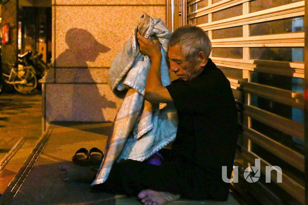 台北市萬華富福里守望相助隊成員(左邊影子)在夜間勸離盤據街頭的遊民(右),希望能...