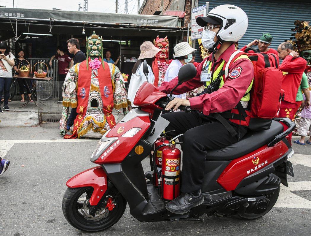 媽祖繞遶境時為避免危險,消防隊如臨大敵,警戒組消防員騎機車來回巡視。 攝影/楊萬...