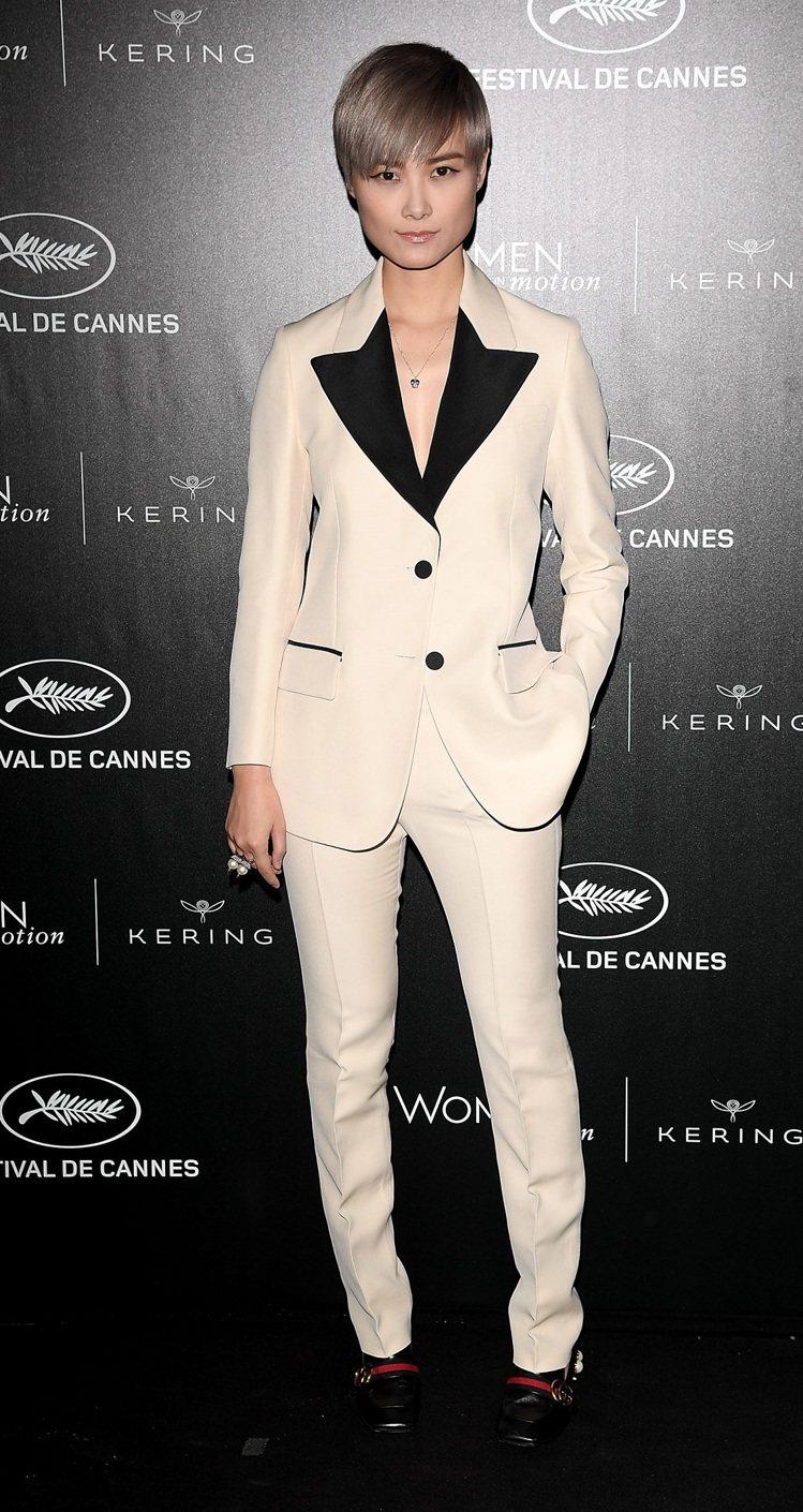 李宇春穿著 Gucci 絲質褲裝,搭配 Gucci 珍珠與鉚釘裝飾戒指、18 K...