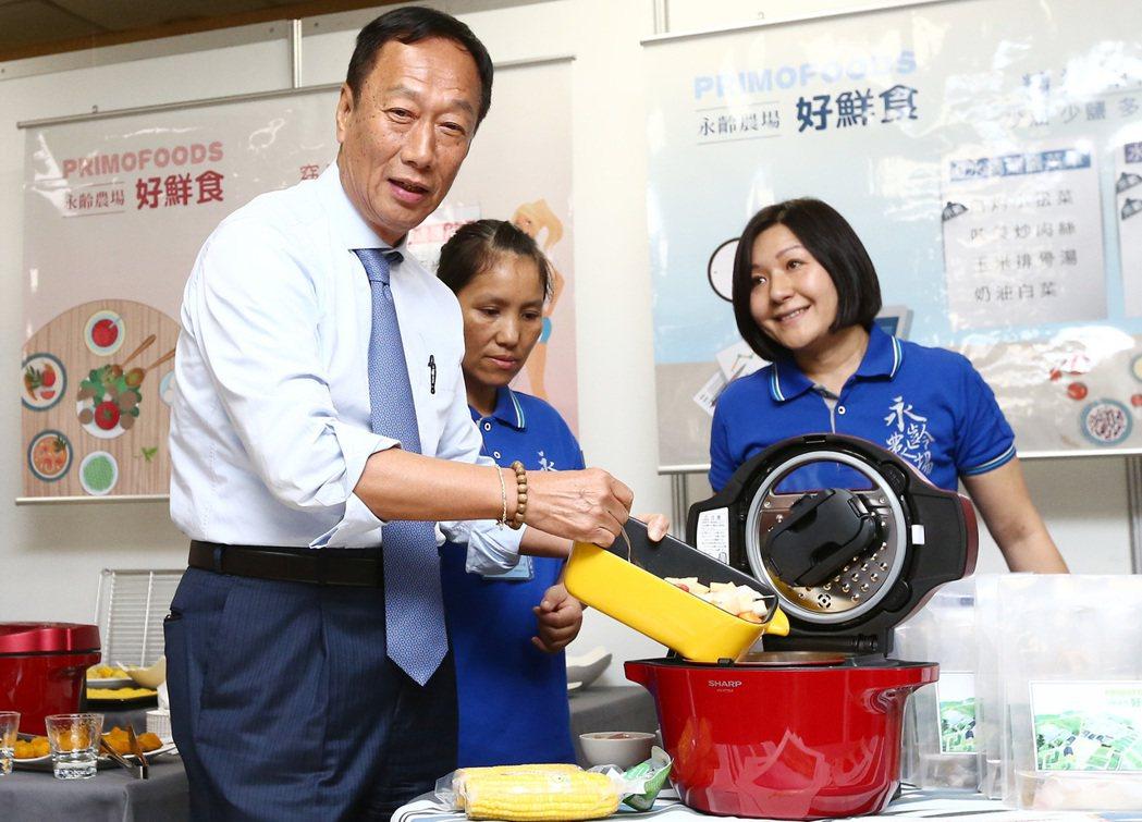 平常不煮飯的鴻海董事長郭台銘(左),在股東會親自用夏普電鍋下廚推銷自家產品。記者...