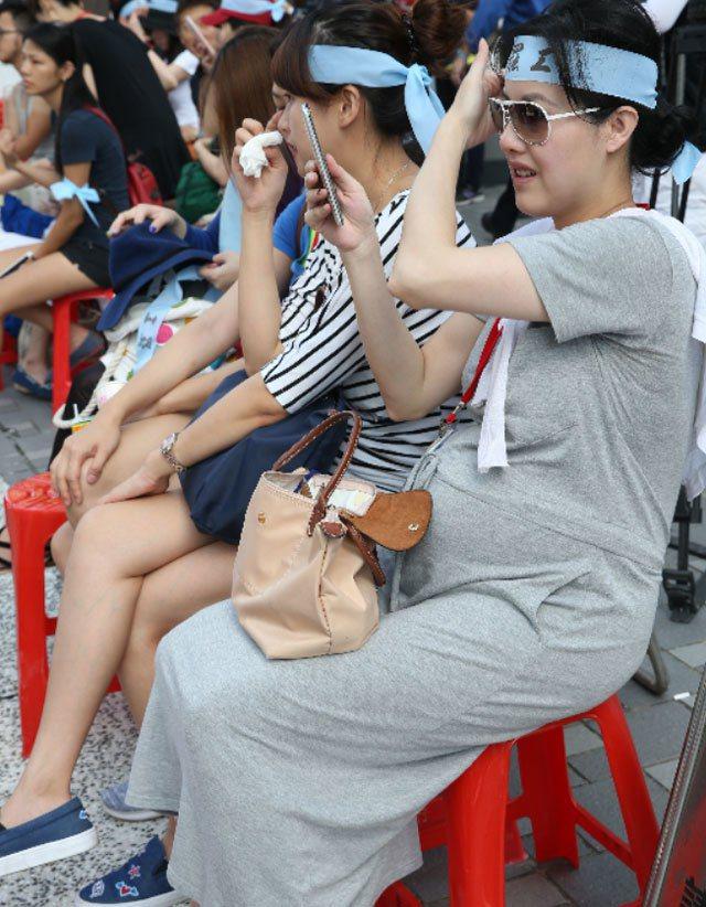 華航空服員上午持續罷工,懷孕的空服員頂著大肚子在烈日下爭取權益。 記者林俊良/...