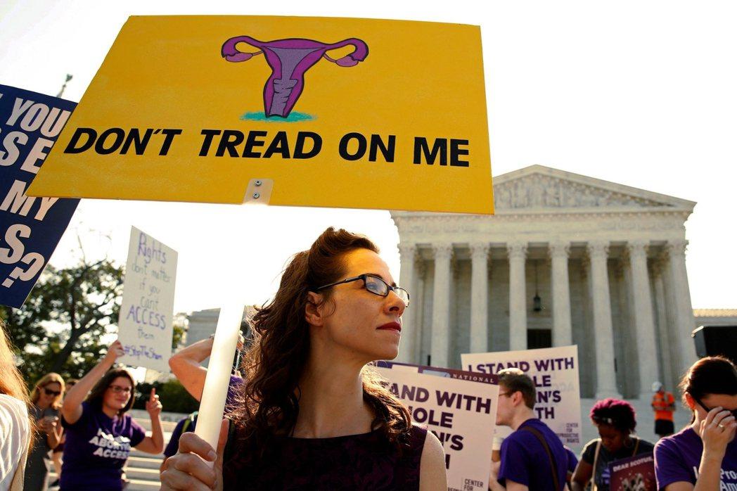 「別糟蹋我。」27日在華府聯邦最高法院外的權利團體,高舉著子宮圖樣的看板,強調生...