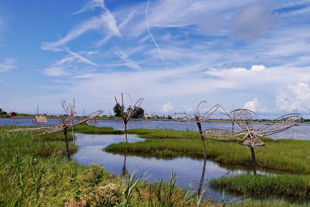 藍天加上濕地景觀,搭配上花卉造型的裝置藝術,更加展現出當地的生命力。 記者陳威任...