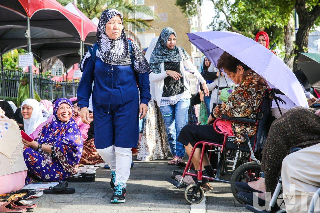 許多外籍勞工把負責看護的老人也帶來現場,只為了順利參加盛會禮拜。記者鄭清元/攝影