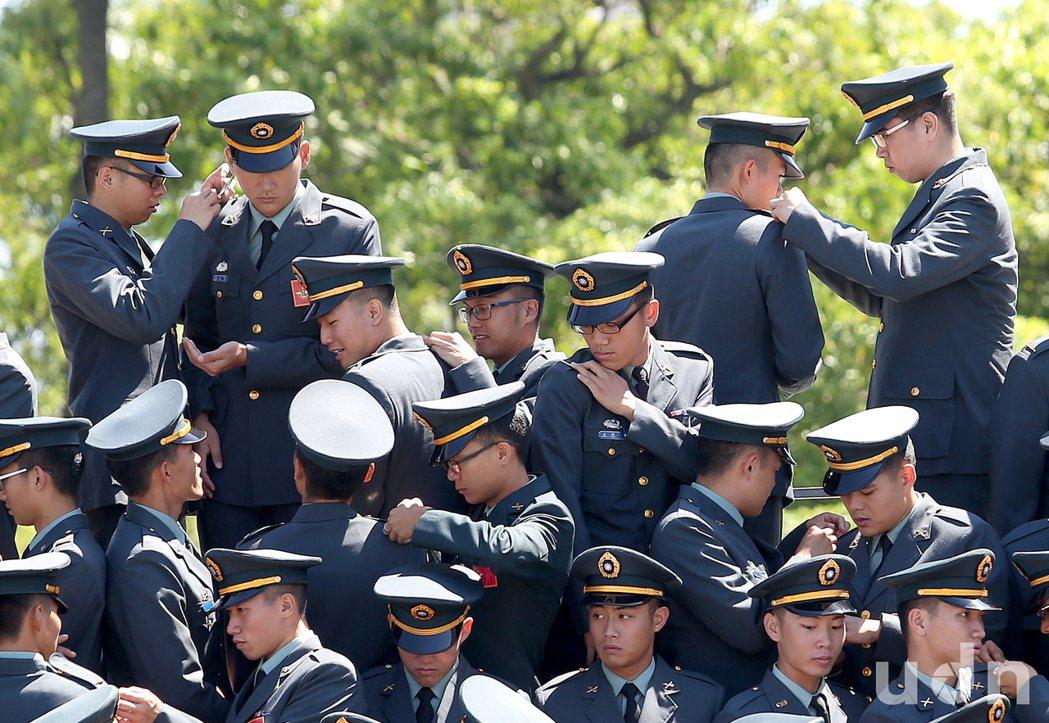 陸軍官校4日舉辦三軍五校聯合畢業典禮,畢業生們在合影前,互相幫忙別上軍階,象徵畢...