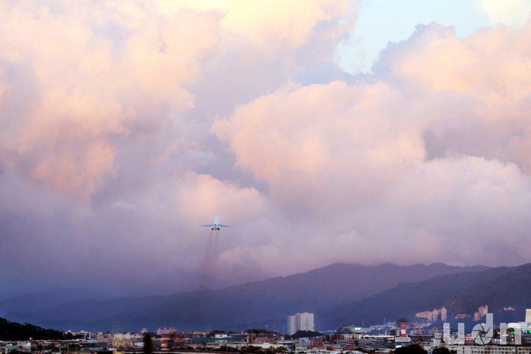 強颱尼伯特即將來襲前,7日台北盆地雲彩詭譎變幻,松山機場飛機起飛後,航向天邊厚厚...