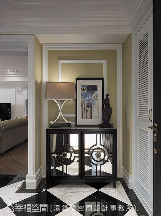 ▲玄關:黑白菱格地坪透過玄關端景櫃的鏡射延伸,拉長玄關線條。