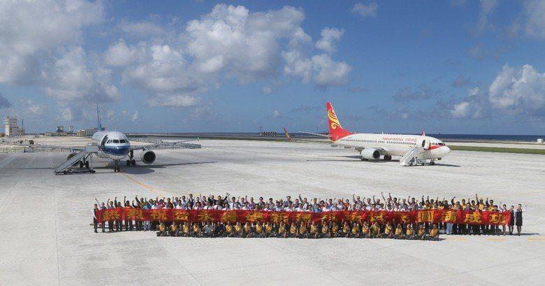 中國在永暑礁機場上拉開布條慶賀試飛成功。 圖/美聯社