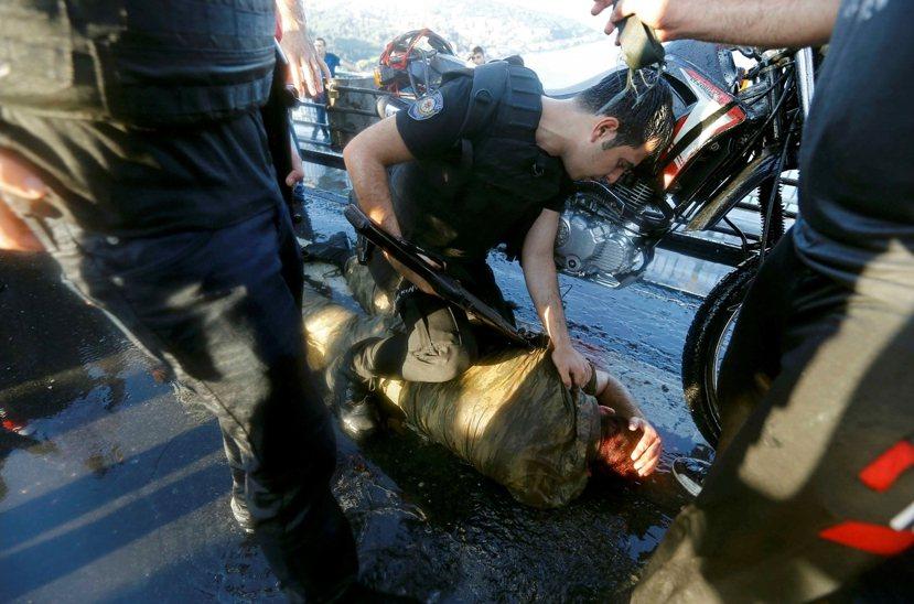 投降後的軍人,遭警方毆打制伏。 圖/路透社