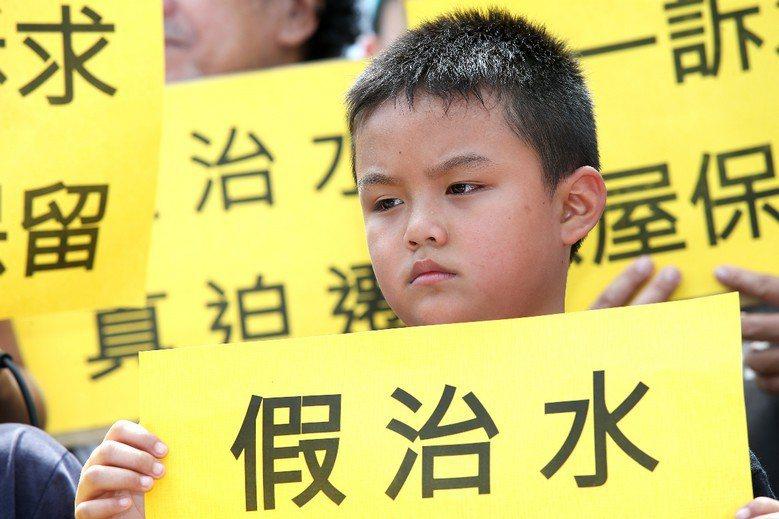 一名小孩舉著「假治水」的標語抗議高雄市政府以治水名義迫遷大溝頂住戶。 攝影/記者...