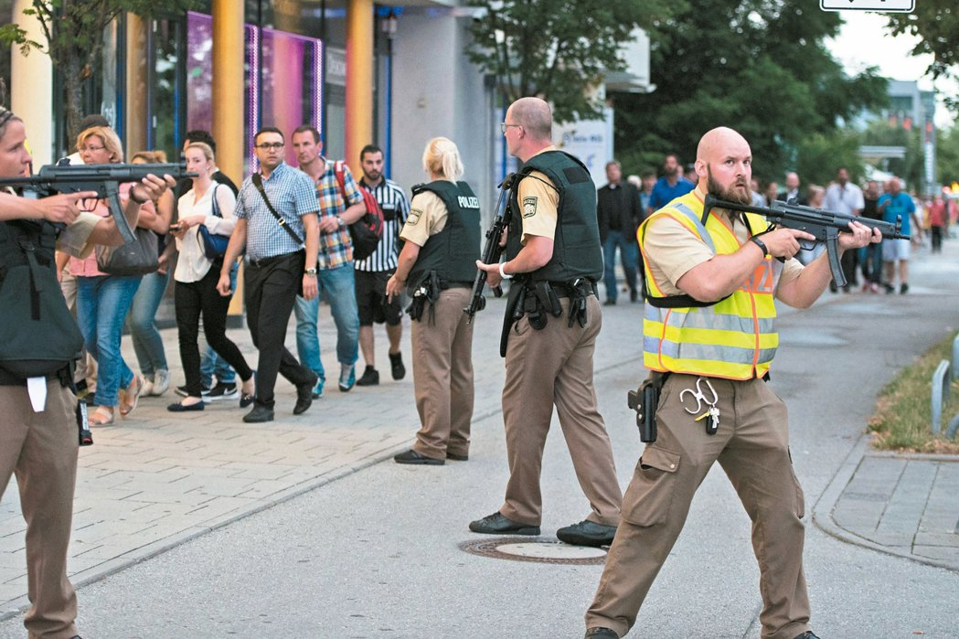 慕尼黑槍擊案發生後,員警荷槍實彈護送民眾離開現場。 美聯社