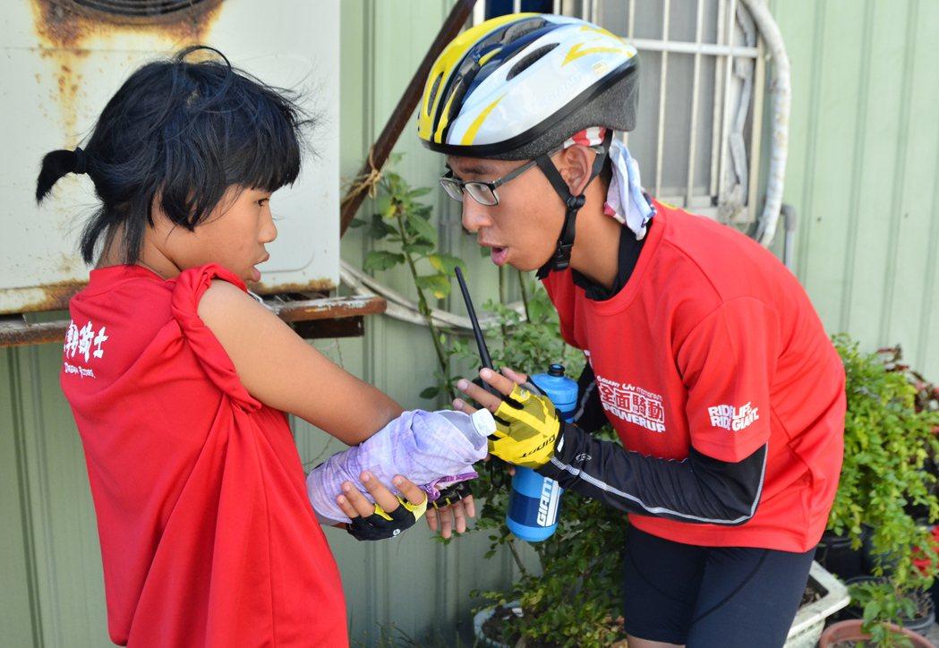 單車環島中,老師觀察手肘擦傷的孩子傷勢後,鼓勵她繼續挑戰環島。彭琬芸/攝