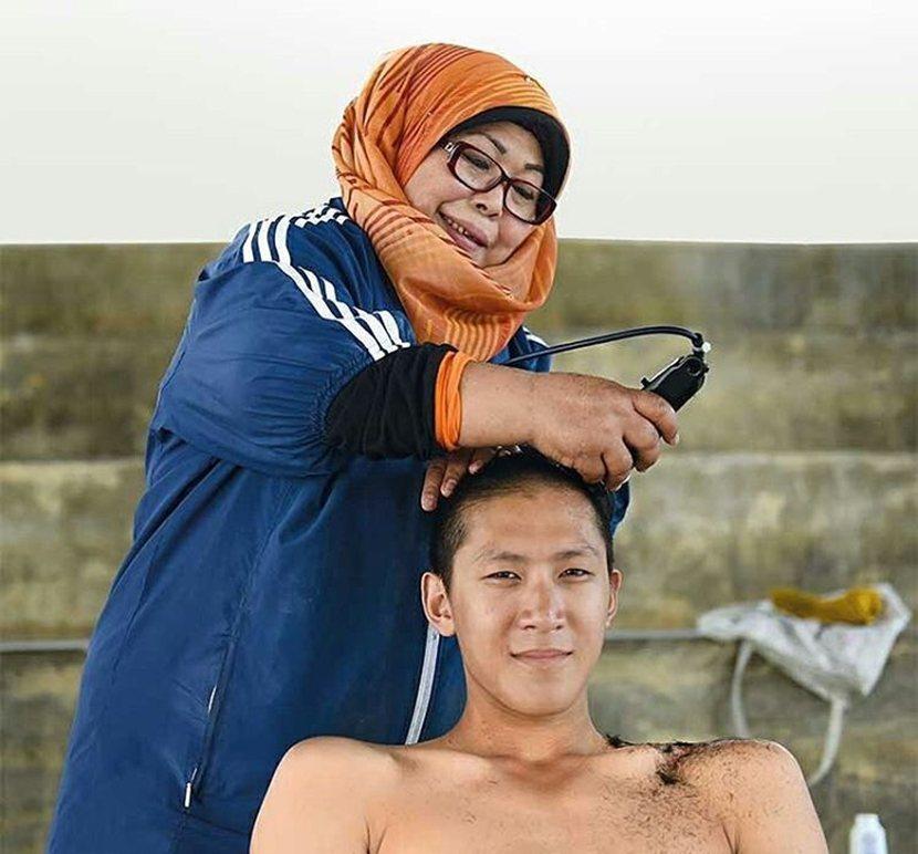 「暫別了,我的自由。」圖:新加坡入伍生與新加坡「髮婆」(部隊從外面請來,專門剃光...