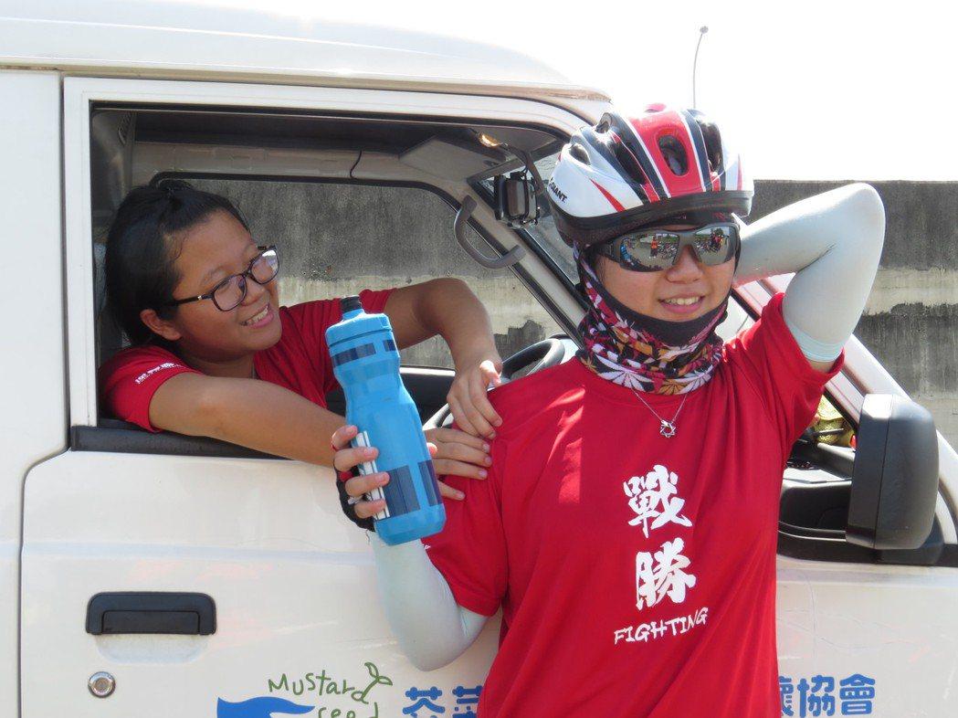 「二寶」張惠甯(左)在休息點時幫妹妹「小寶」張詠淇(右)按摩。圖/楊雅棠攝影。