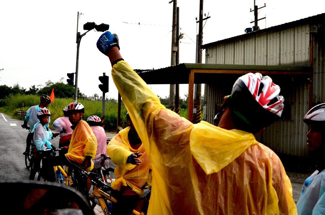 三峽小草書屋車隊騎乘間播放音樂,老師洪浩中在下雨天為孩子加油打氣。彭琬芸/攝