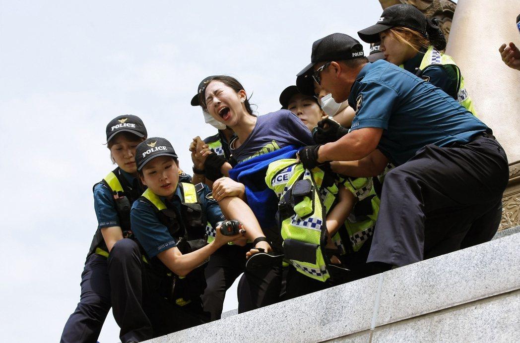 2016年7月12日,首爾光化門廣場,一名派遣工自救會的示威者與警方在世宗大王銅...