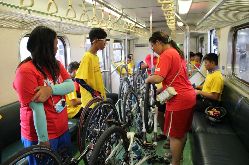 成員合力將腳踏車倒立放好。攝影/簡鈺璇