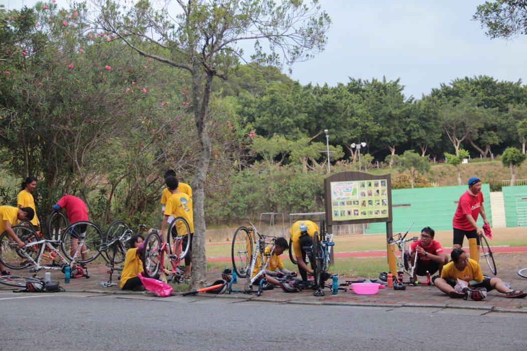 騎士在終點旁擦拭車子,感謝它陪伴自己一千公里的旅程。特約記者簡鈺璇/攝影