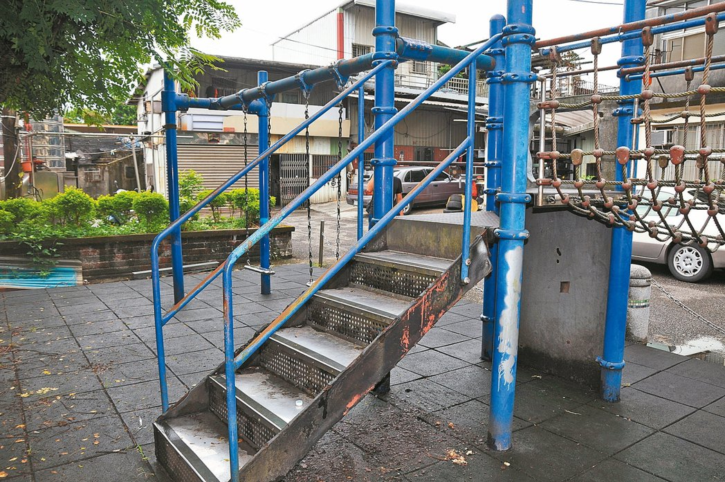 金華街一處兒童遊樂場要爬上溜滑梯的鐵製梯子鏽蝕嚴重,鐵鏽掉滿地。 記者游明煌/攝...