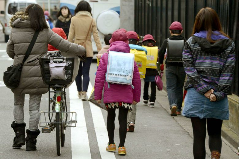 台灣小學放學時間經常可以看到幫小孩背書包的父母,但在日本多讓孩童自己背。 圖/美...