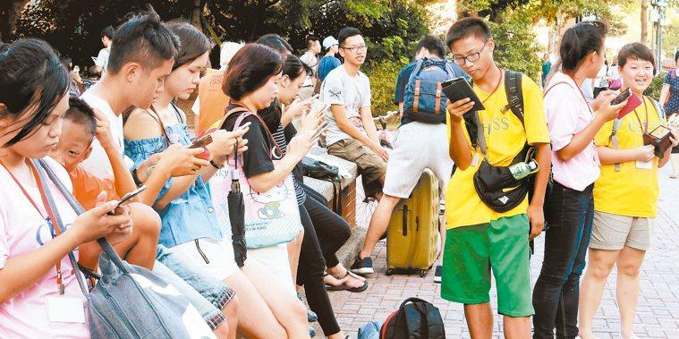 手機遊戲《精靈寶可夢》在台上線後,路上隨處可見民眾滑手機抓寶。 報系資料照