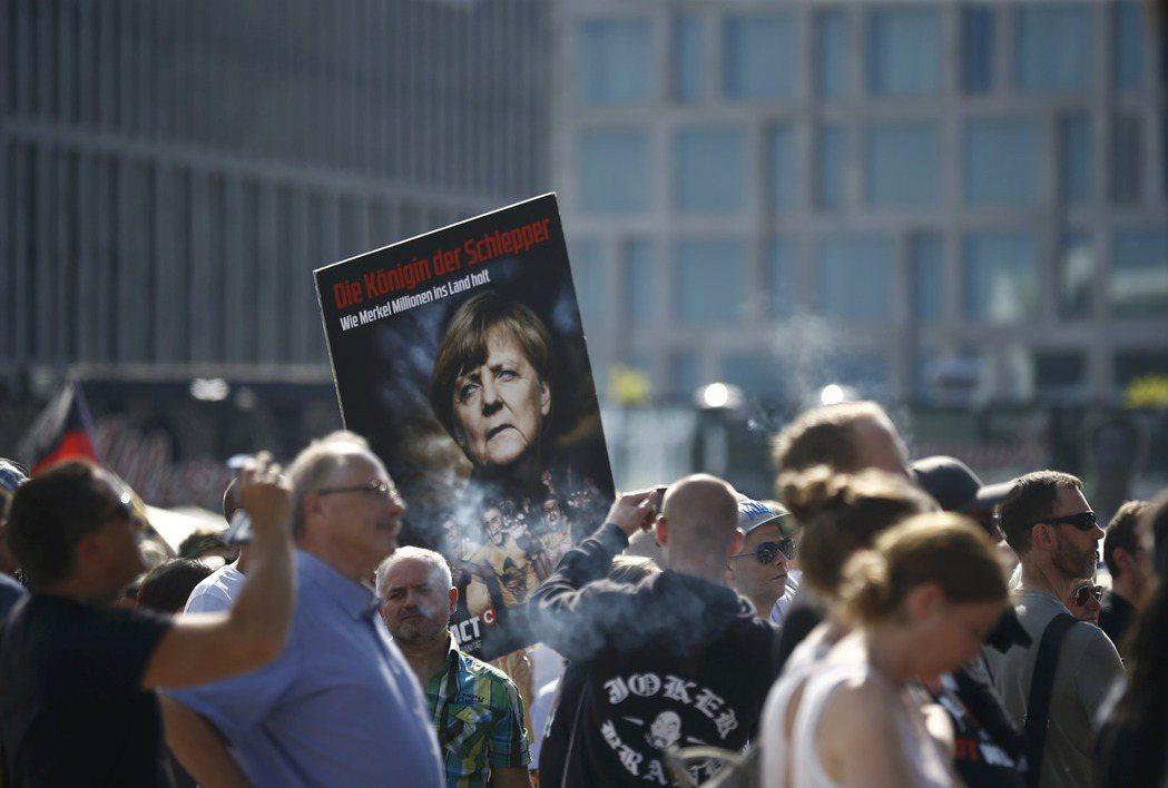 柏林街頭「我們為柏林也為德國」抗爭活動,群眾們高舉著總理梅克爾的立牌,上頭寫著「...