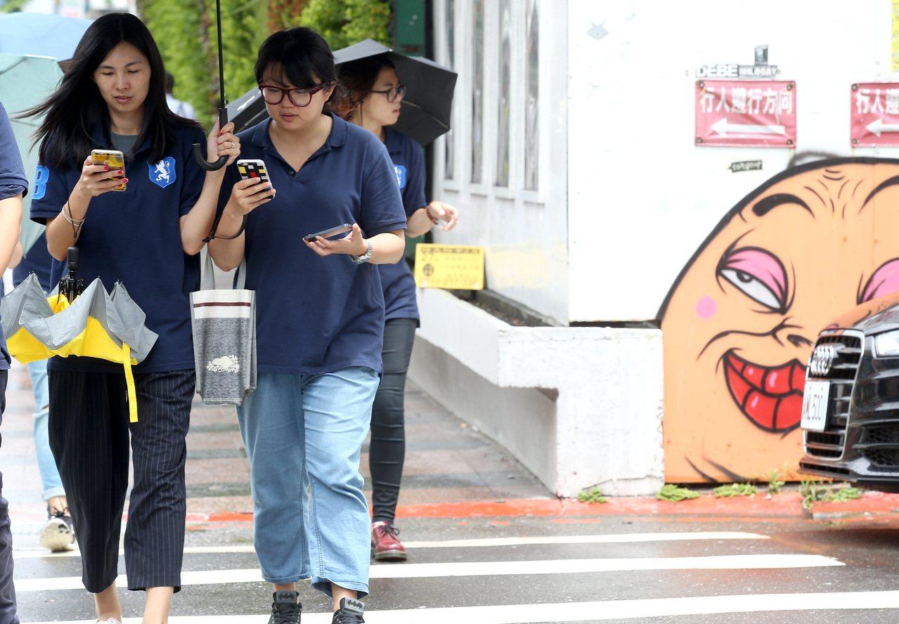 隨著寶可夢熱潮,路上行人低頭滑手機的狀況越來越多。圖/高彬原