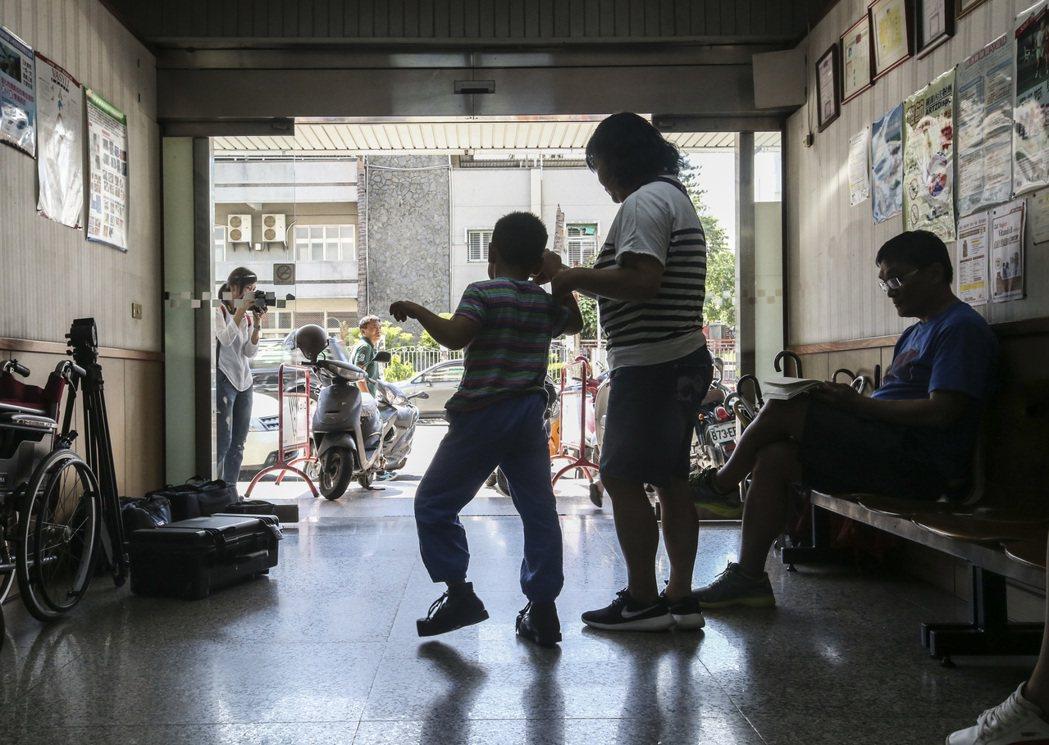林秉嬋牽著政勳走出復健診所,陪孩子面對現實。 記者楊萬雲/攝影
