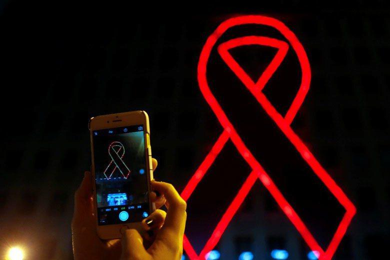 衛福部疾病管制署在世界愛滋日於外牆懸掛巨型紅絲帶燈飾點燈儀式,象徵對愛滋病患的關...