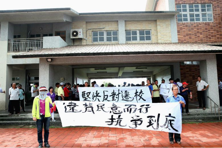 許厝分校開學當日,反對遷校的家長在校舉起布條表達反對意見。 攝影/林俊良