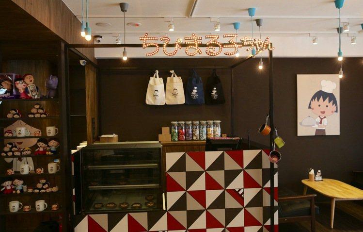櫃檯上有大大的櫻桃小丸子標誌,牆面上掛著帆布袋、徽章等限定授權商品。記者陳柏亨/...