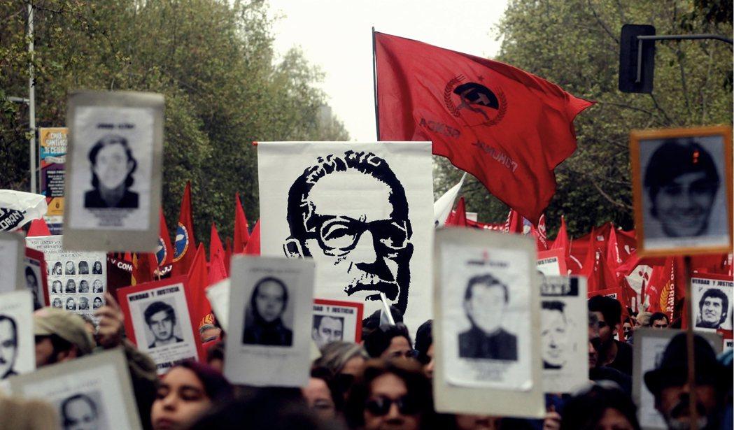 聖地牙哥街頭的紀念遊行,群眾們高舉著獨裁迫害受難者的遺照,與殉難的總統阿葉德的肖...