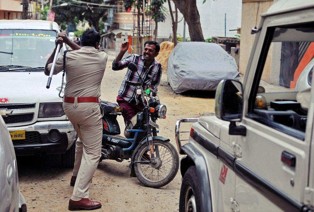 水源暴亂讓「印度矽谷」班加羅爾全城實施宵禁,圖為驅逐違反宵禁令民眾的警察。 圖/...