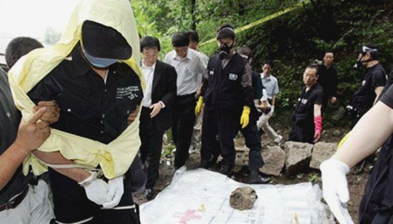 柳永哲被捕之後,帶著警方到埋藏屍體的現場。當天下著大雨,柳永哲穿著黃色雨衣、帶上藍色口罩遮住臉龐,站在一旁安靜的看著挖掘出的受害者遺體。 圖/取自ohmynews