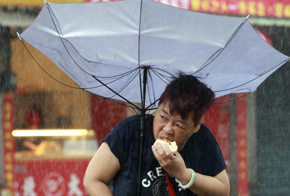「傘開花啃肉包姨」無懼颱風天風雨,大口吃著肉包。 美聯社