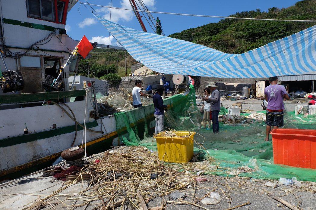 垃圾卡在漁網上難以清除,需一個個用手拉扯下來。記者張芮瑜/攝影