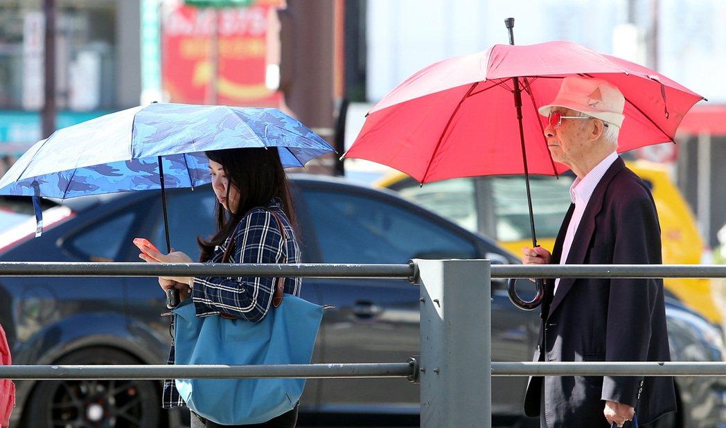 出外民眾無論男女老幼皆撐起傘,遮蔽炙熱陽光的照射。記者侯永全/攝影