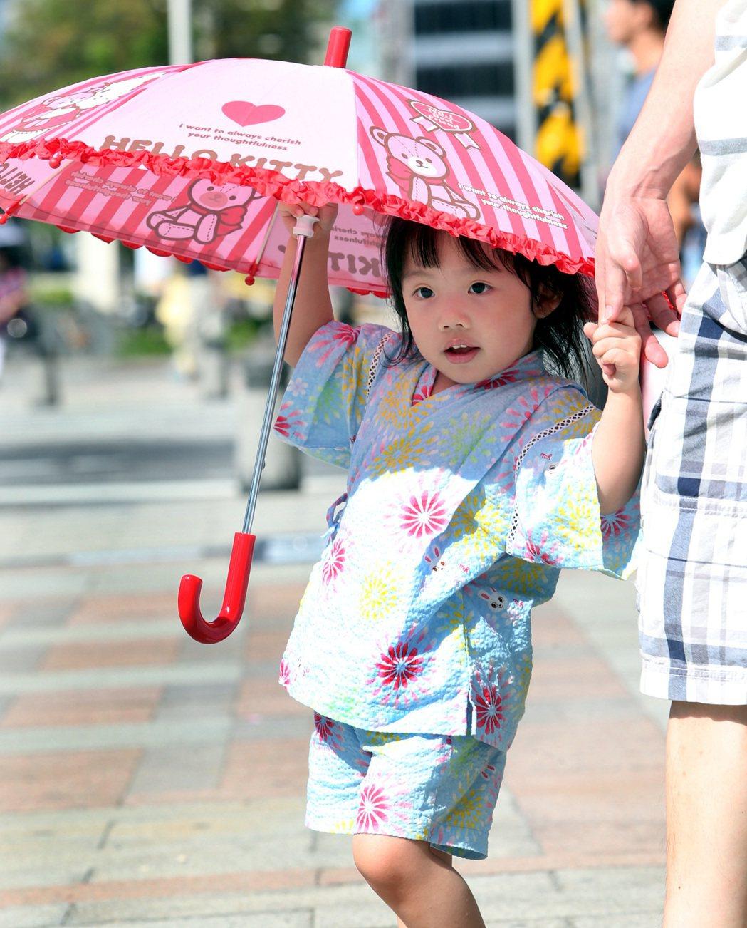 烈日當頭,一名穿著小和服的小娃牽著爸爸手撐傘遮陽。記者侯永全/攝影