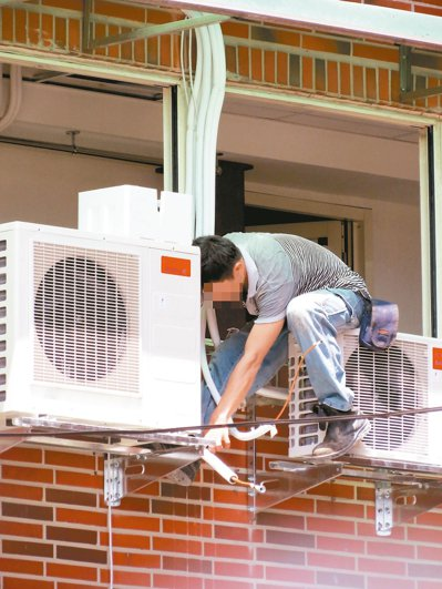 不少房屋並未設計冷氣室外機設置空間,技師常需攀爬在大樓外牆施工,非常危險。 記者...